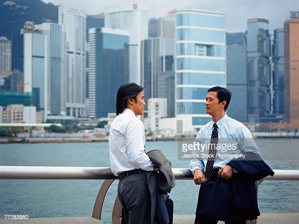 Two businessmen standing by river and talking