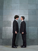 Two businessmen standing face to face, side view