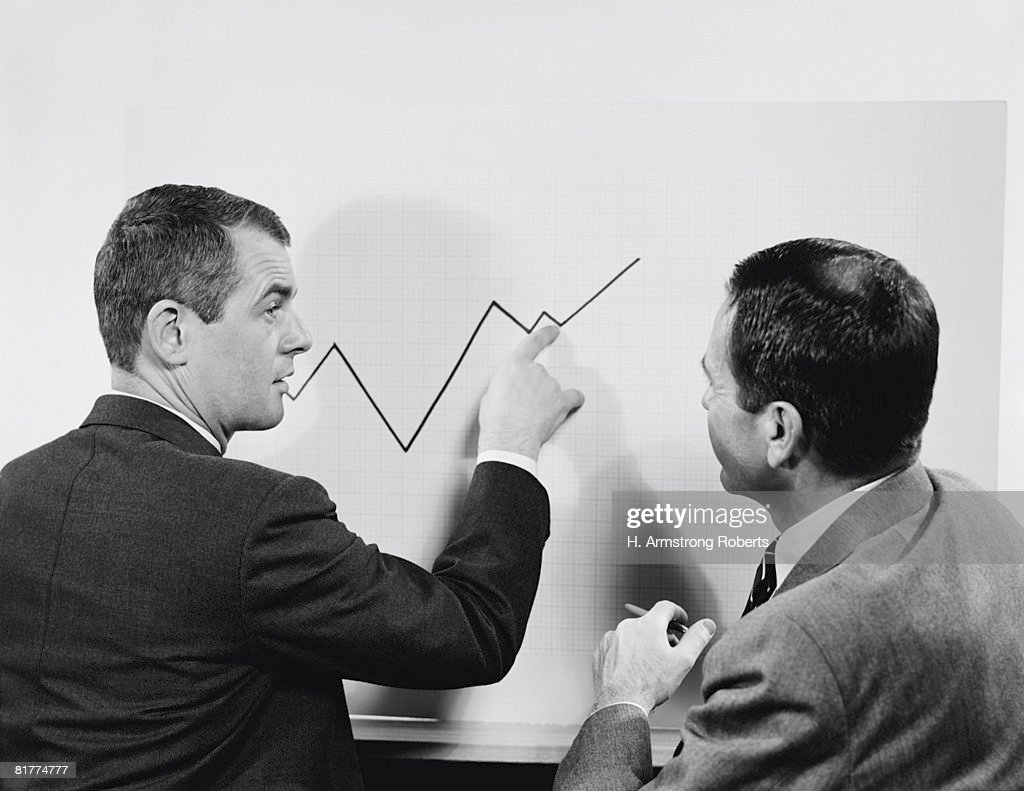 Two businessmen standing in front of chart graphic, pointing to line, peaks and valleys showing growth. : Stock Photo
