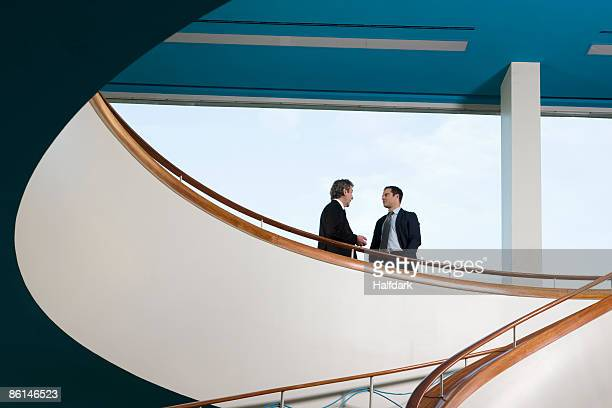 Two businessmen standing on a balcony and talking