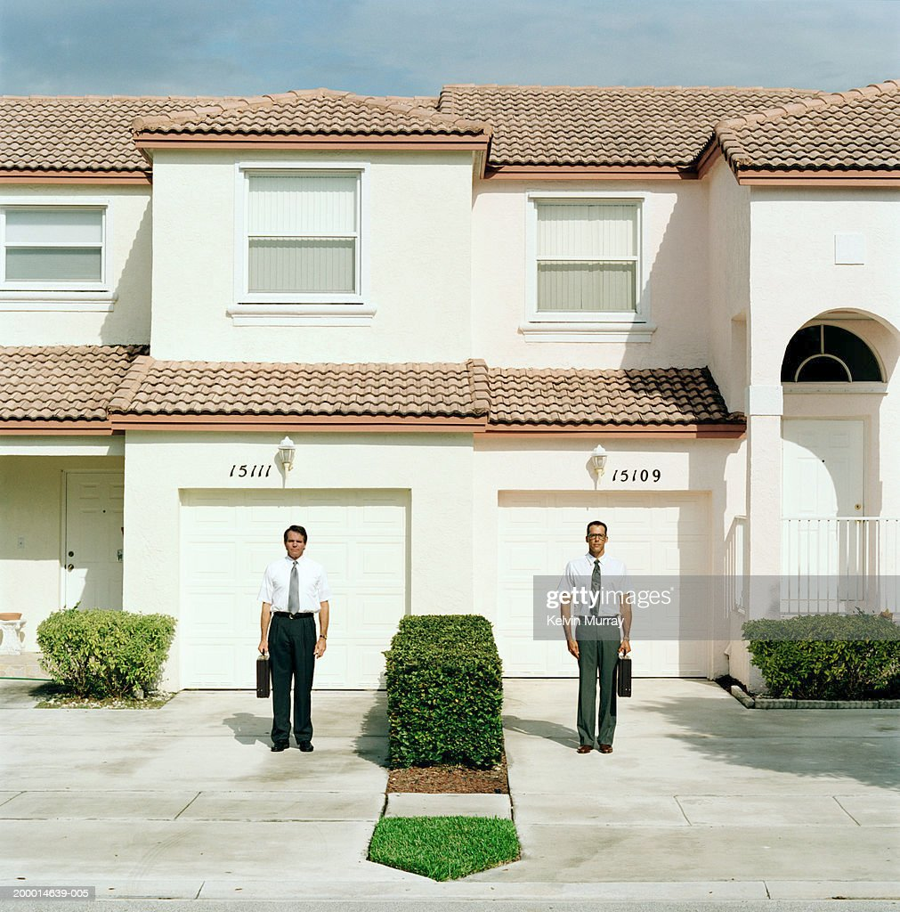 Two businessmen standing outside houses