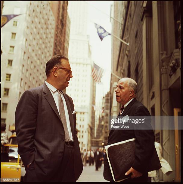 Two businessmen stop to talk on Wall Street in the Financial District New York USA ca 1961