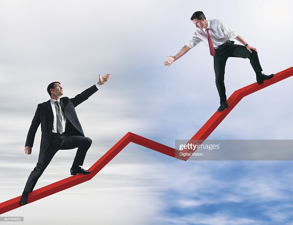 Two Businessmen Stretching Their Arms Out to Bridge the Gap : Stock Photo