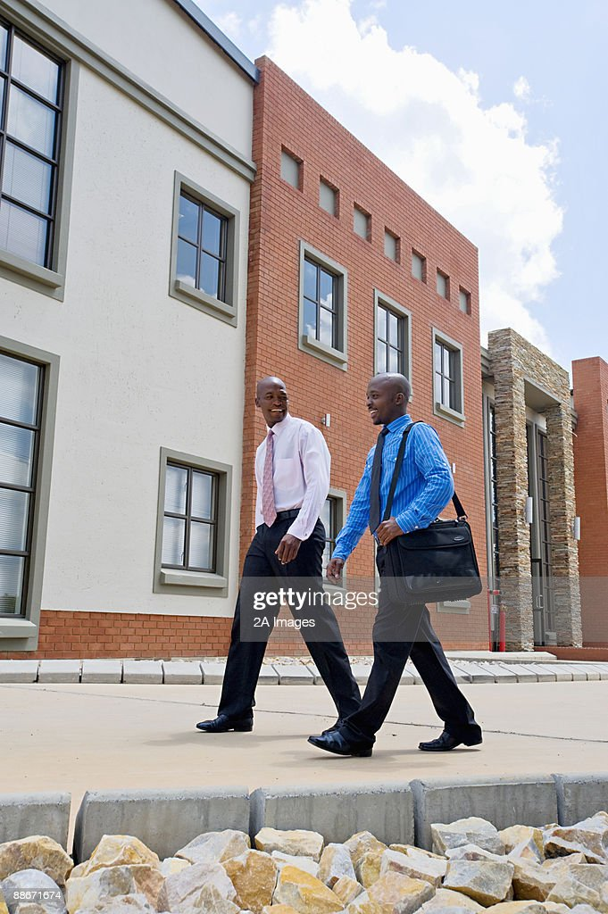 Two businessmen talking and walking through an office park. Pretoria, South Africa : Stock Photo