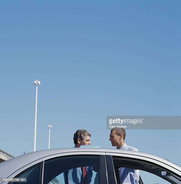 Two businessmen talking by car