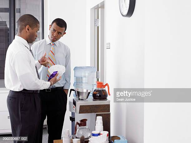Two businessmen talking by office coffee machine