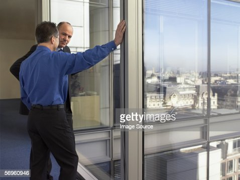 Two businessmen talking by window : Stock Photo