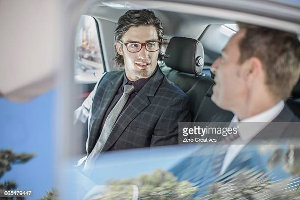 Two businessmen talking in car back seat