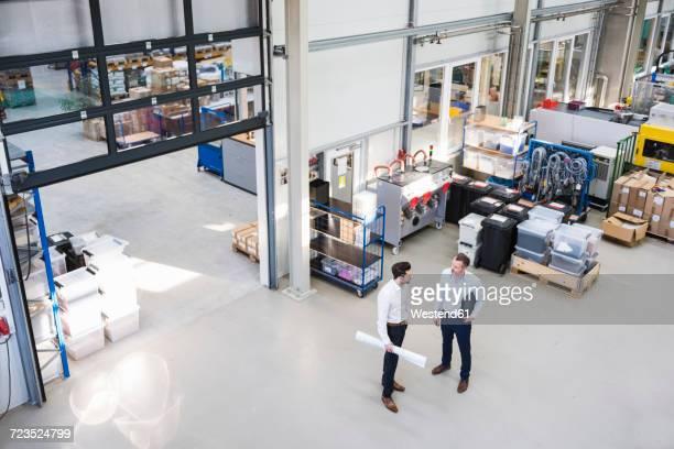Two businessmen talking in factory shop floor