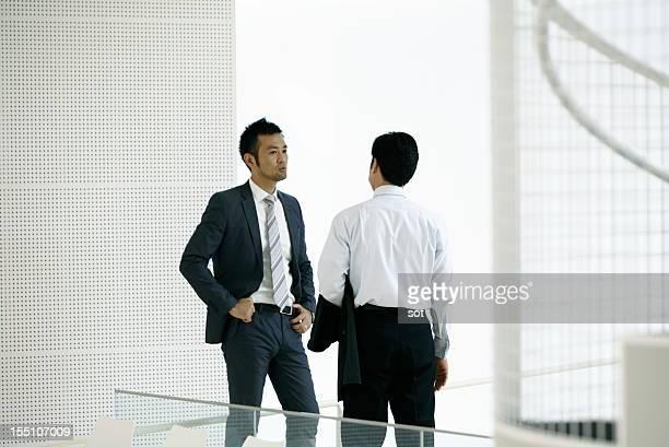 Two businessmen talking in office hallway