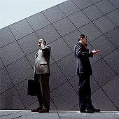 Two businessmen talking on cell phones on sidewalk