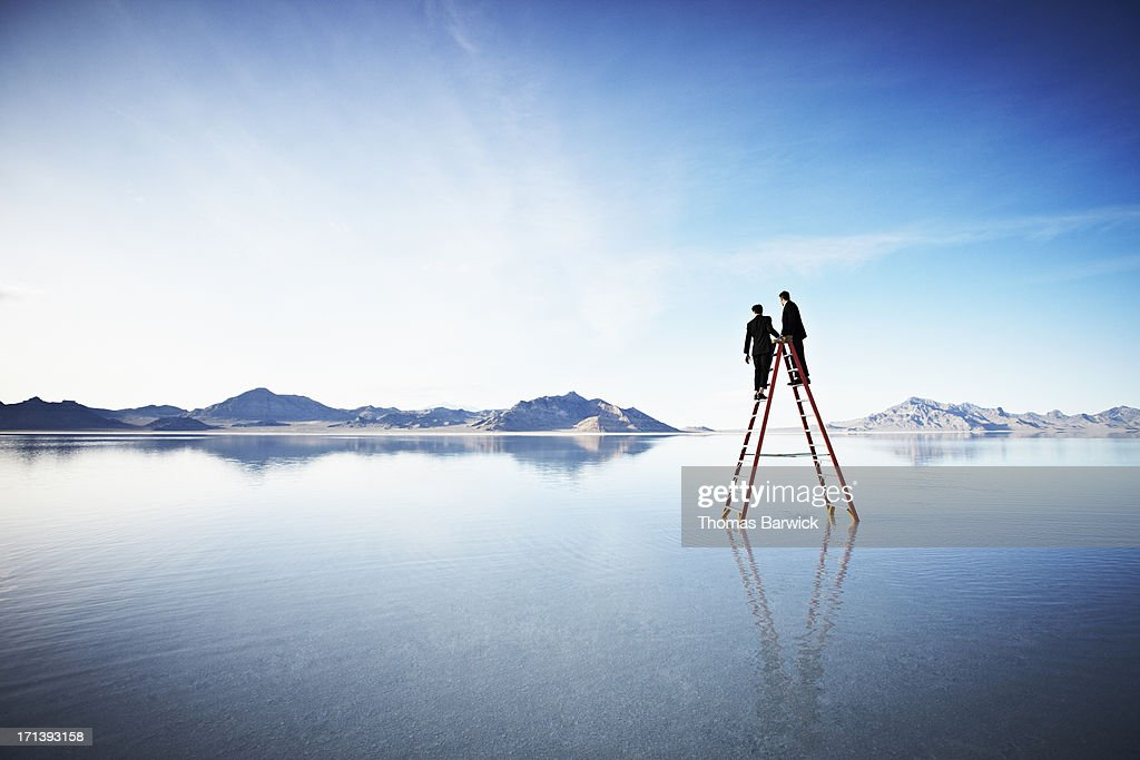 Two businessmen together on top of ladder in lake : Stock Photo