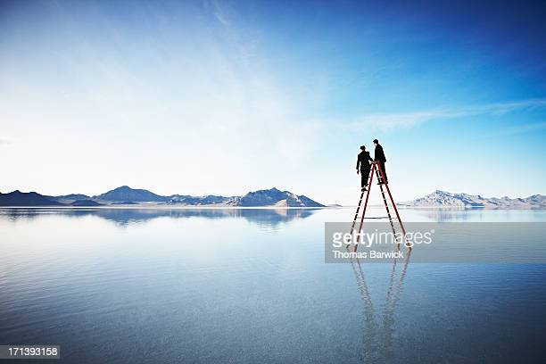 Two businessmen together on top of ladder in lake