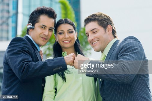 Two businessmen touching knuckles and a businesswoman smiling : Foto de stock