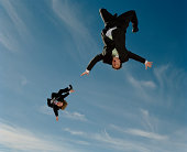 Two businessmen upside down in mid-air (blurred motion)