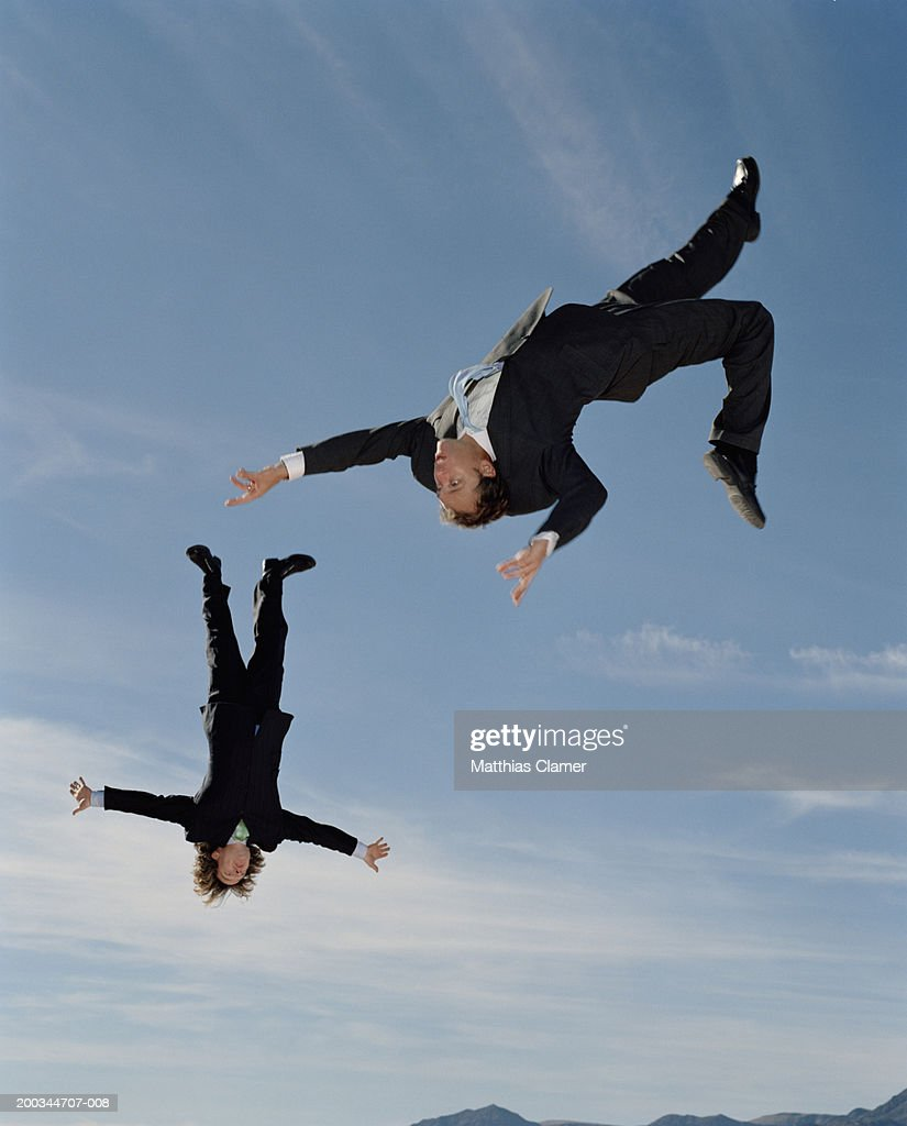 Two businessmen upside down in mid-air