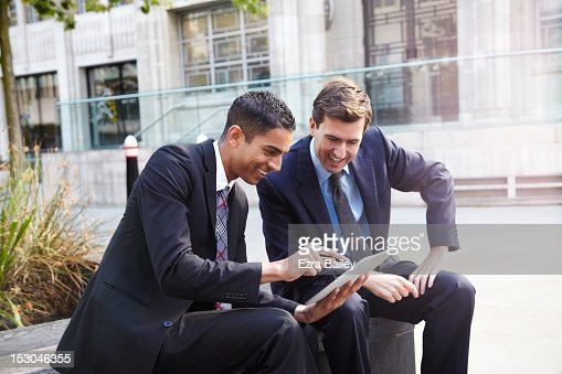 Two businessmen using a tablet outside. : Stock Photo