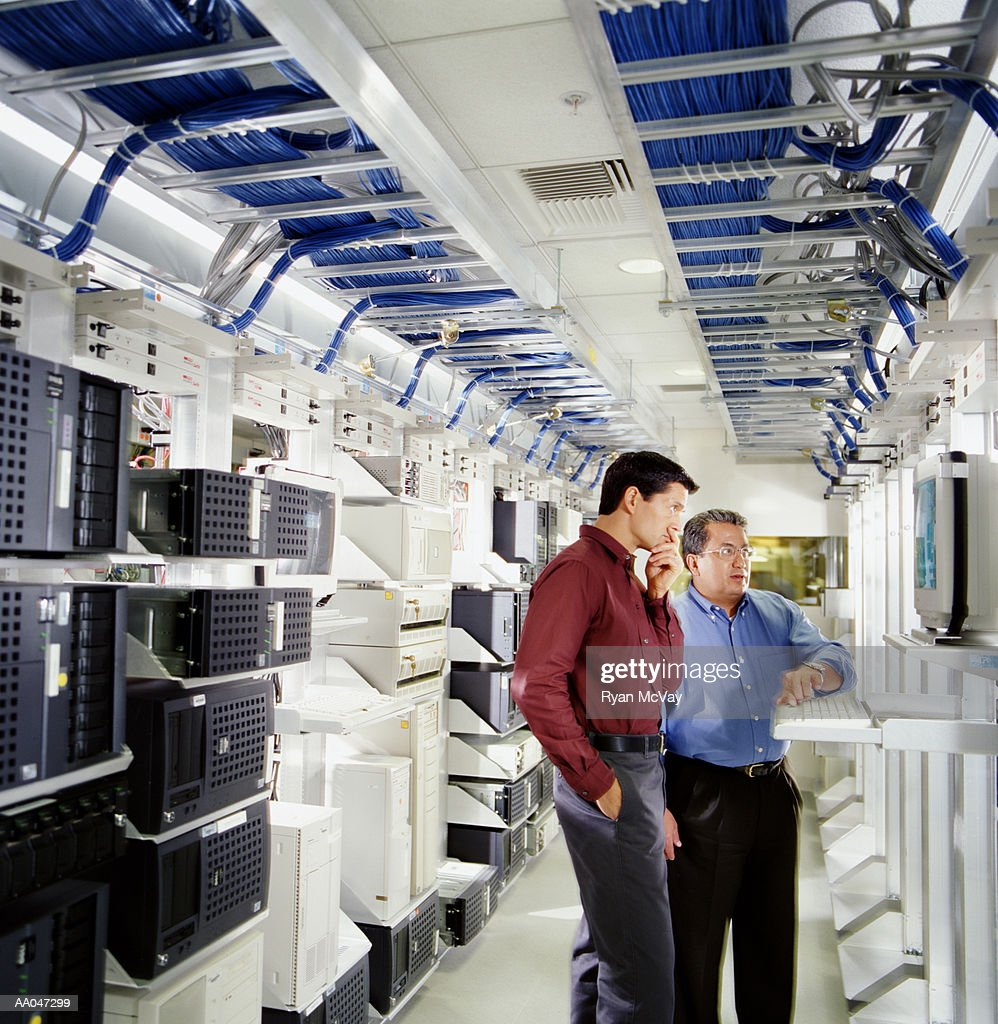 Two businessmen using computer in server room : Stock Photo