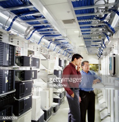 Two businessmen using computer in server room : Stock-Foto