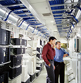Two businessmen using computer in server room