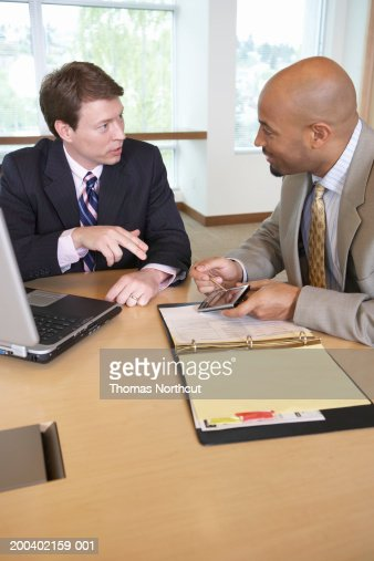 Two businessmen using laptop and palmtop while talking in meeting : Stock Photo
