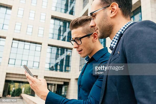 Zwei Geschäftsleute mit smartphone für Firmenmeetings in office building