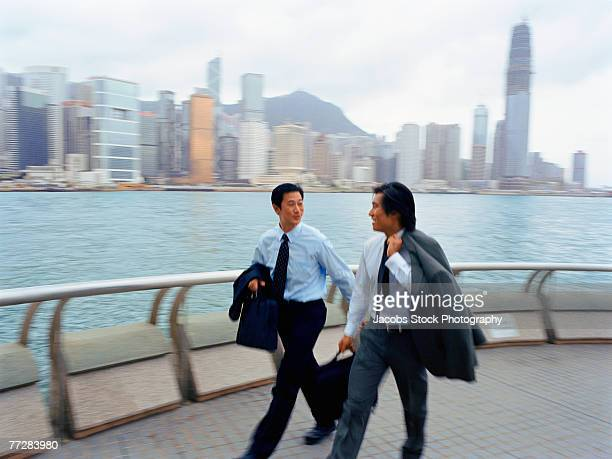 Two businessmen walking by waterfront