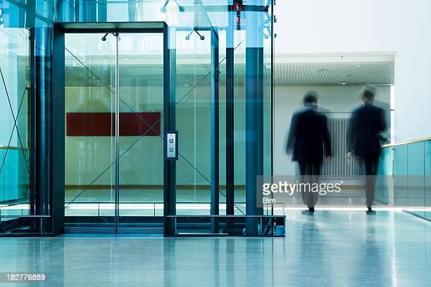 Two Businessmen Walking in Office Corridor, Blurred Motion