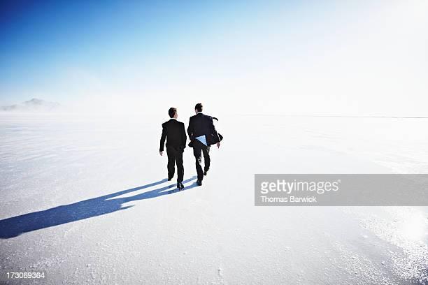 Two businessmen walking on salt flats rear view