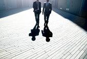Two businessmen walking through the city.
