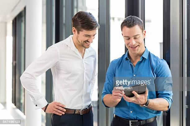 Two businessmen watching digital tablet in an office
