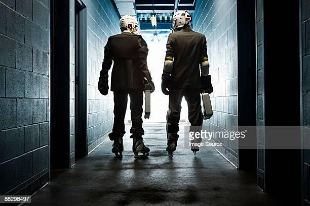 Two businessmen wearing ice hockey uniforms