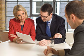 Two businessmen with a businesswoman talking in a meeting
