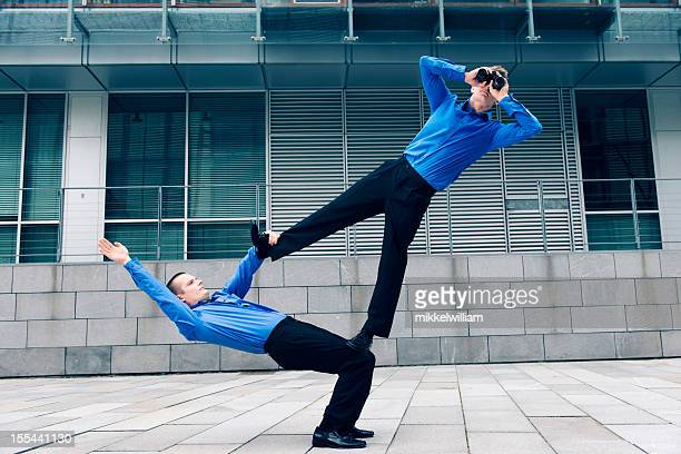 Two businessmen with acrobatic skills work together