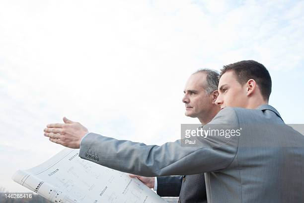 Two businessmen with architectural plan talking outdoors