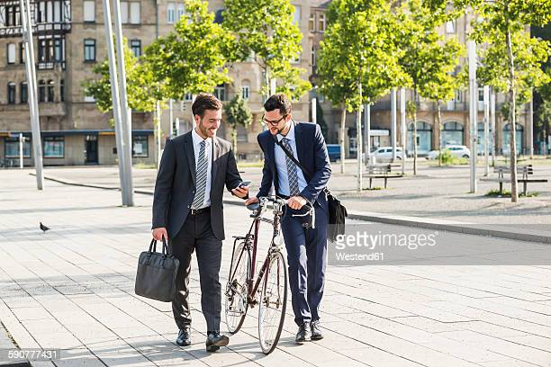 Two businessmen with bike and smart phone walking in the city