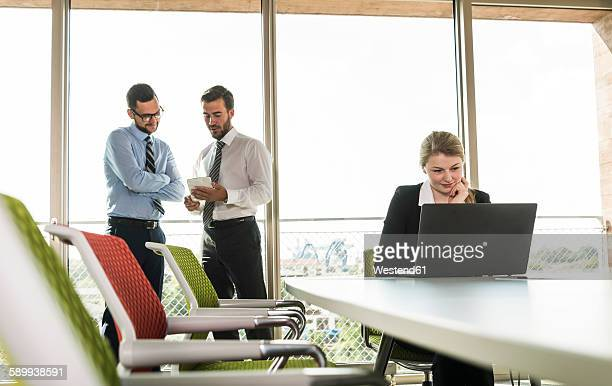 Two businessmen with digital tablet and businesswoman with laptop in conference room