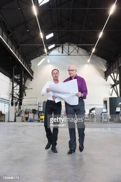 Two businessmen with plan walking in factory shop floor