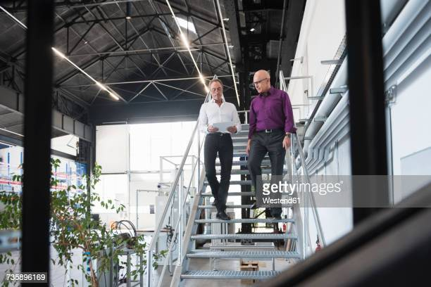 Two businessmen with tablet walking down stairs in factory shop floor