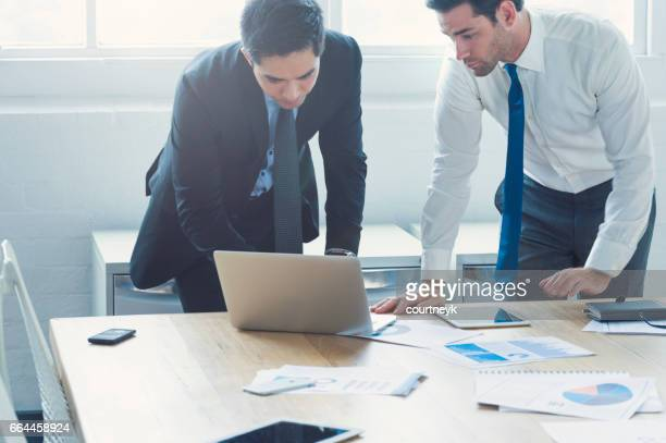 Two businessmen working on laptop computer.