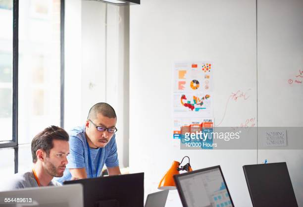 Two businessmen working together at the computer