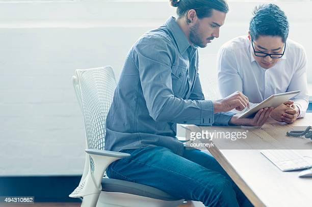 Deux hommes d'affaires travaillant avec une tablette numérique.