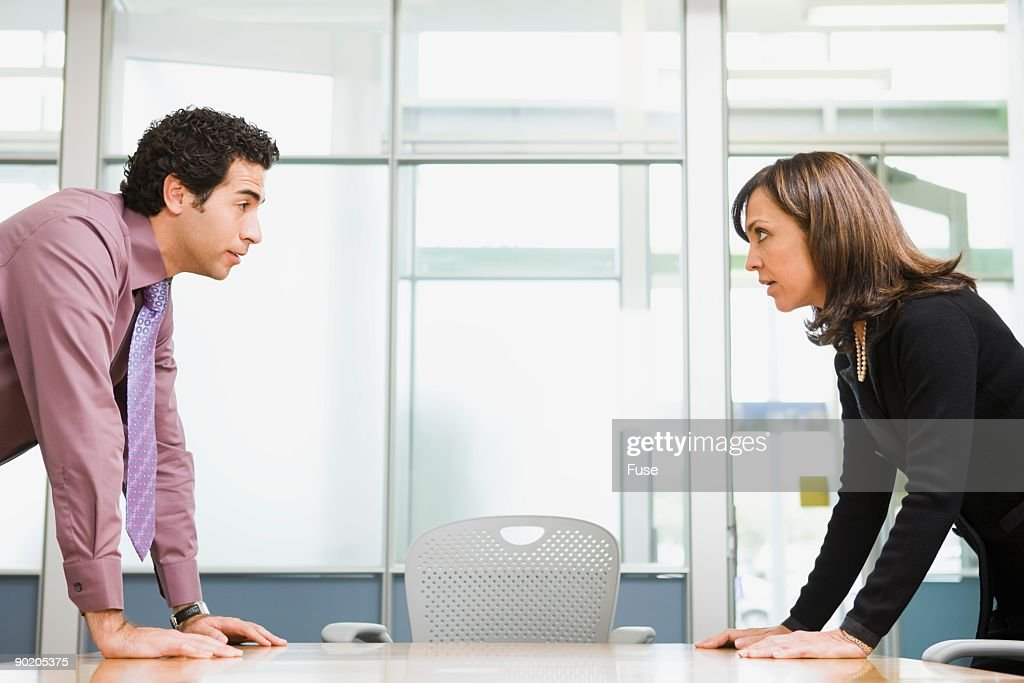 Two businesspeople facing off over conference room table