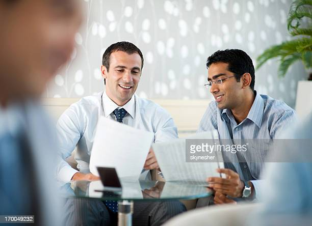 Two businesspeople holding reports