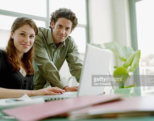 Deux hommes d'affaires dans le Bureau avec ordinateur portable souriant