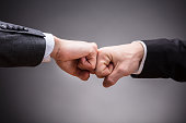 Close-up Of Two Businesspeople Making Fist Bump Against Grey Background