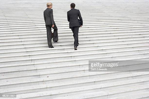 Two businesspeople outdoors going up staircase