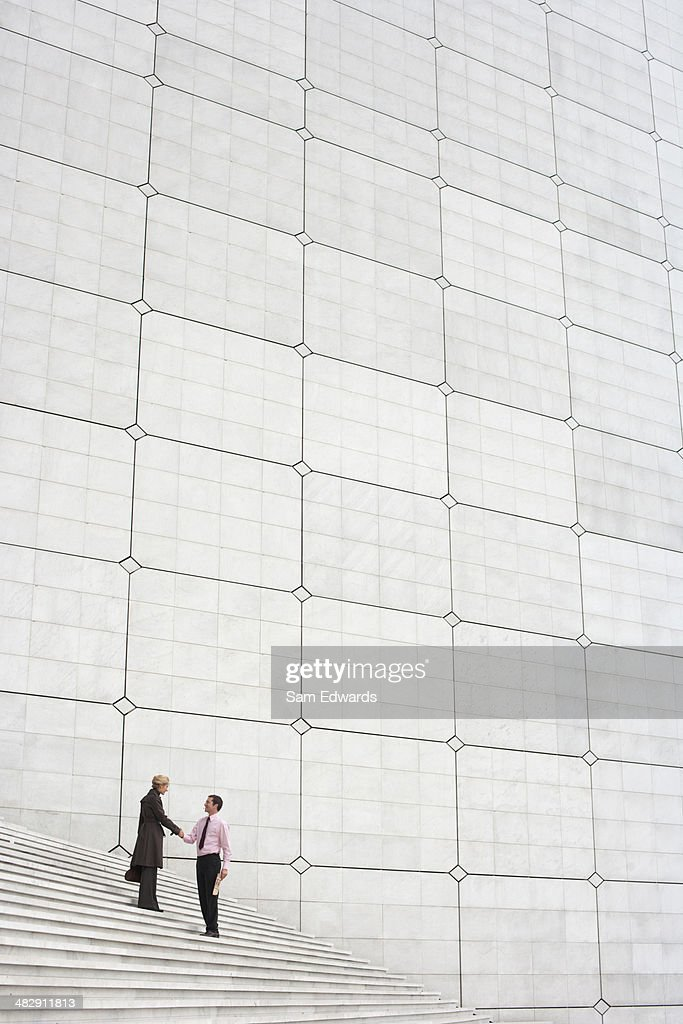 Two businesspeople outdoors on staircase shaking hands