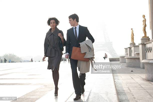 Two businesspeople outdoors walking by building near Eiffel Tower