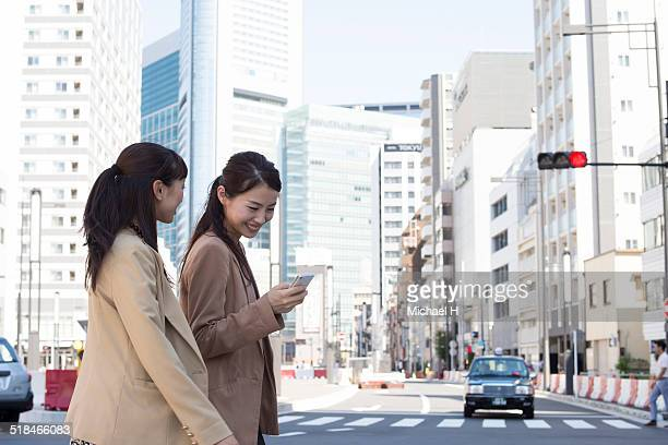 Two businesspeople outdoors walking in office town